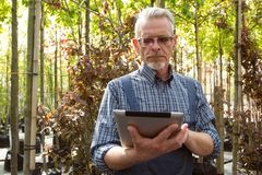 Online Store Manager with a clipboard in hands on a background of a greenhouse royalty free stock image