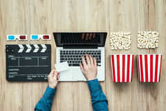 Online streaming cinema. Man holding a ticket and watching a film streaming online with popcorn, 3D glasses and clapboard, movies and cinema concept royalty free stock image