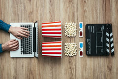 Online streaming cinema. Man watching a film streaming online with popcorn, 3D glasses and clapboard, cinema and entertainment concept, flat lay Royalty Free Stock Photo