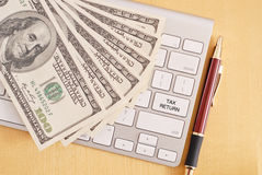 Online Tax Returns. Tax Return Key with Pile of Money Stock Photo