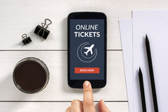 Online tickets concept on smart phone screen with office objects. On white wooden table. All screen content is designed by me Stock Photo