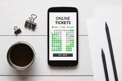 Online tickets concept on smart phone screen with office objects. On white wooden table. All screen content is designed by me. Flat lay Stock Photos