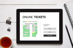 Online tickets concept on tablet screen with office objects. On white wooden table. All screen content is designed by me. Flat lay Stock Photos