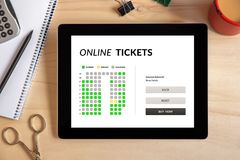 Online tickets concept on tablet screen with office objects. On wooden desk. All screen content is designed by me. Top view Royalty Free Stock Photography
