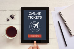 Online tickets concept on tablet screen with office objects. On white wooden table. All screen content is designed by me Stock Photo