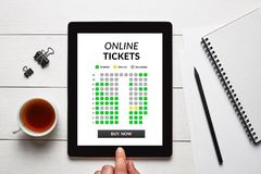 Online tickets concept on tablet screen with office objects. On white wooden table. All screen content is designed by me. Flat lay Stock Photography