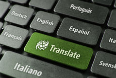 Online translation service concept. Multilingual translation online concept. Close up of multi language keyboard and translate word key in green color with Royalty Free Stock Photos