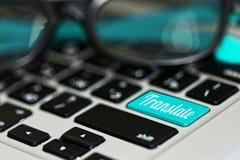 Online translator concept. Online translator idea - macro close-up capture of laptop keyboard with translate key on it and eyeglasses. Blue color accent Stock Images
