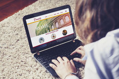Online travel agency in a laptop computer. Top view of laptop with travel website on the screen. Person searching for travel destination on the internet Stock Photo