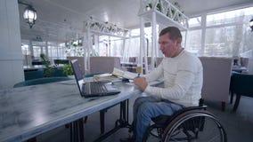 Online-utbildning, studenthandikappade personerman på rullstolen använder modern bärbar datorteknologi för att lära från online-k arkivfilmer