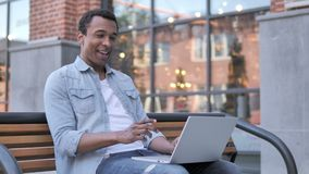 Online video chat on laptop by african man sitting on bench stock footage