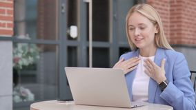Online video chat on laptop by young businesswoman sitting outdoor. 4k high quality, 4k high quality stock video footage
