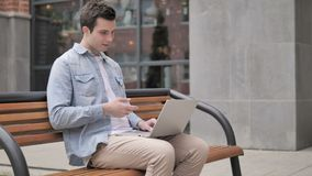 Online video chat on laptop by young man sitting on bench stock footage
