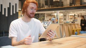 Online Video Chat by Redhead Beard Man on Tablet PC in Cafe stock video