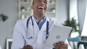 Online Video Chat on Tablet by African-American Doctor stock footage