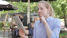Online Video Chat on Tablet by Young Woman Sitting in Cafe Terrace stock video