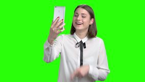 Online video conversation on the phone using web cam. Green screen hromakey background for keying stock footage