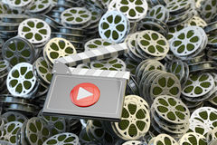 Online video, movie and media player, multimedia collection background. Clapper board with play button at the heap of retro film reels Stock Photos