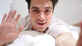 Online-video pratstund av mannen som ligger i säng, slut upp Royaltyfria Foton