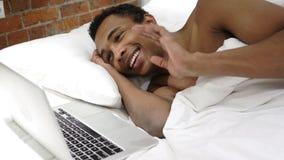 Online-video pratstund på bärbara datorn av den afrikanska mannen som ligger i säng Arkivbild