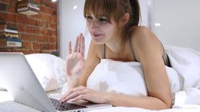 Online-video pratstund på bärbara datorn av kvinnan som ligger i säng på natten Royaltyfri Foto