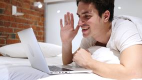 Online-video pratstund på bärbara datorn av mannen som ligger i säng på natten Arkivfoto