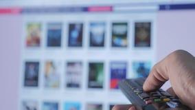 Online-video strömmande service med apps och handen Smart TV Manliga det avlägsna handinnehavet kontrollen vänder av smart tv stock video