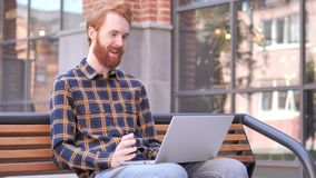 Online Videopraatje op Laptop door de Jonge Mensenzitting van de Roodharigebaard op Bank stock videobeelden