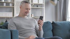 Online Videopraatje op Smartphone door Gray Hair Man Te ontspannen stock videobeelden
