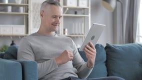 Online Videopraatje op Tablet door Gray Hair Man Relaxing op Laag stock videobeelden