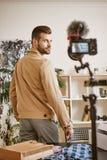 Online Winkelend Achtermening van jonge mannelijke manier die blogger beige jasje dragen terwijl het registreren van nieuwe video stock fotografie