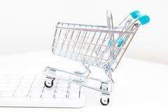 Online winkelend, Desktop met boodschappenwagentje stock foto