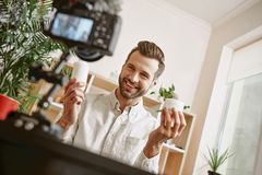 Online Winkelend Vrolijke jonge mannelijke blogger die nieuwe videoblogepisode over nieuwe cosmetischee producten registreren stock fotografie