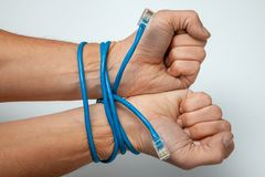 Online work, dependence on the Internet. Male hands wrapped with twisted pair blue cable on gray background royalty free stock photo