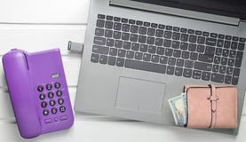 Online work, freelancing concept. Office phone, laptop, flash drive, wallet on a white wooden table.Top view.  royalty free stock photos