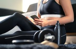 Online workout course, personal trainer service or fitness app in phone. Fit woman using smartphone while working out at home.