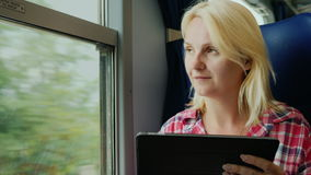 Always online. Young woman enjoys a tablet on the train. A young woman is traveling on a train. Sits by the window, uses a digital tablet. 4K video stock video