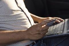 Online-Zahlung, die Hände des Mannes, die eine Kreditkarte mit der Anwendung des Laptops für das on-line-Einkaufen in der Sonnens Lizenzfreie Stockfotografie