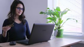Online-Zahlung, junges Mädchen mit Plastikkarte schließt Kauf auf Internet durch Computer ab stock video footage