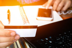 Online-Zahlung, man& x27; s übergibt das Halten einer Kreditkarte über Laptop Lizenzfreie Stockfotos
