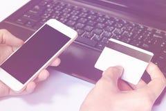 Online-Zahlung, man& x27; s übergibt das Halten einer Kreditkarte über Laptop Stockfotos