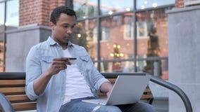Online zakupy Afrykańskim mężczyzny obsiadaniem na ławce zbiory wideo