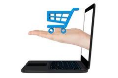 Online zakupy pojęcie. Wózek Na Zakupy ikona w ręce z laptopem fotografia stock