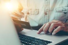 Online zapłata, mężczyzna ` s ręki trzyma caredit karciany i używa laptop fotografia stock