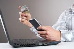 Online zapłata, mężczyzna ` s wręcza trzymać kredytową kartę i używać mądrze laptop & telefon Zdjęcia Stock