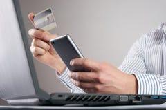 Online zapłata, mężczyzna ` s wręcza trzymać kredytową kartę i używać mądrze telefon Fotografia Royalty Free