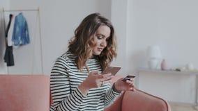 Online zapłaty przez interneta od bank karty Zbliżenie portret elegancka ładna dziewczyna Ona używa smartphone i zbiory