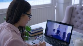 Onlinetraining, aantrekkelijke jonge vrouw in glazen met pen die in blocnote tijdens het letten op video op laptop schrijven stock video