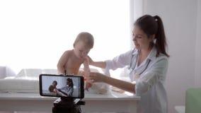 Onlinetraining, beroemde vloggermeisje arts die sociale media video op celtelefoon registreren tijdens algemeen medisch onderzoek stock video