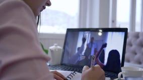 Onlinetraining, vrouwelijke gebruikende laptop computer voor videoonderwijs en verre het werk bespreking die nota's in notitieboe stock video